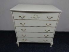 A cream and gilt five drawer chest