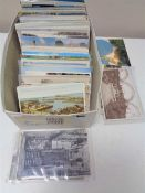 A box of early twentieth century and later colour and black and white postcards