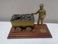 A welsh brass mining figure with cart on wooden board