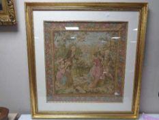 A gilt framed tapestry depicting figures in a garden