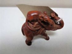 A carved fruitwood netsuke in the form of a rat riding an elephant
