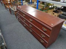 A mahogany effect three drawer chest together with a pair of three drawer bedside chests