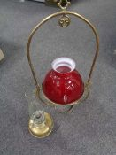 A brass Art Nouveau hanging oil lamp with glass shade and chimney