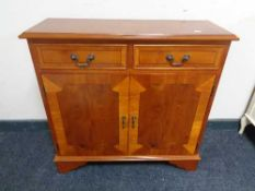 An inlaid yew wood double door cabinet fitted with two drawers above