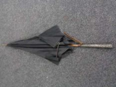 An antique parasol with silver handle
