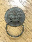 An antique Chinese bronze door handle, diameter 9.5 cm, total drop from top to bottom 14 cm.