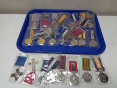 A tray of reproduction British war medals on ribbons
