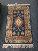 A machine made fringed hearth rug on blue ground. 132 cm x 75 cm.