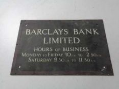 A brass Barclays bank limited business hours plaque