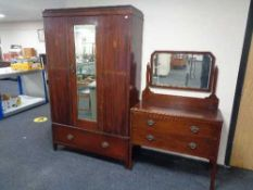 An Edwardian inlaid mahogany mirrored wardrobe fitted with a drawer and a two drawer dressing chest