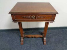 A reproduction mahogany work table with under stretcher and column supports