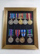 Nine reproduction military medals on ribbons in frame