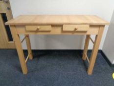 A pine effect side table fitted with two drawers
