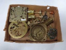 A box of assorted brass ware, trivets, goblets,