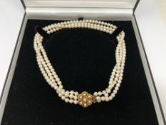 A triple strand cultured pearl necklace with gold clasp,