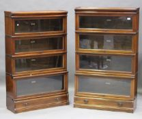 A pair of early 20th century walnut four-section Globe Wernicke library bookcases, each fitted