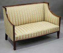 An Edwardian mahogany and boxwood inlaid salon settee, upholstered in a striped damask, height 83cm,