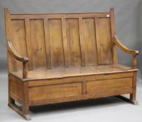 A 19th century provincial pine panelled back settle, the box seat and scroll arms raised on sledge