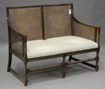A George V oak framed bergère settee, the slightly double-bowed back and sides with caned panels, on