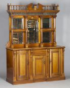 An Edwardian walnut side cabinet, the swan neck and turned balustrade pediment above a concave