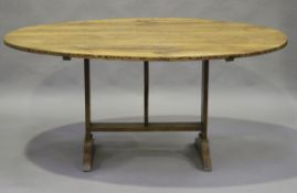 A late 19th century French fruitwood tilt-top vendange or wine tasting table, the oval top on a