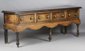 An 18th century and later oak dresser base, fitted with two drawers flanking two later hinged doors,