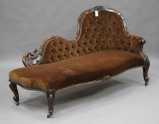A Victorian walnut carved showframe chaise-longue, upholstered in buttoned chocolate brown velour,