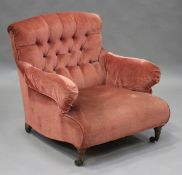 A late Victorian buttoned back scroll armchair, probably by Howard & Sons, raised on turned and