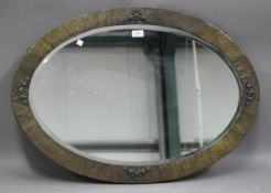 An early 20th century hammered brass oval wall mirror, 83cm x 59cm.Buyer's Premium 29.4% (