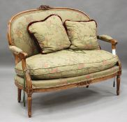 A late 20th century Louis XVI style stained beech showframe two-seat settee, upholstered in a