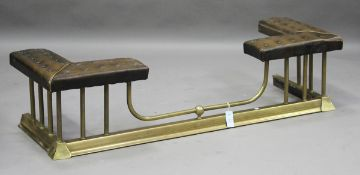 An early/mid-20th century brass club fender, the seat upholstered in buttoned brown leatherette,