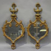 A pair of late 19th century Rococo Revival carved softwood wall mirrors, the frames with urn finials