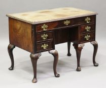 A George II mahogany kneehole desk, the crossbanded top with a carved edge above drawers and central