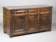 A mid-18th century provincial oak dresser base, fitted with three drawers above arched panel