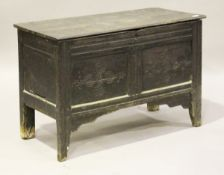 A late 17th century oak panelled coffer, the lid with original wire hinges above a carved front,