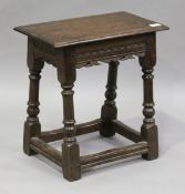 A 20th century Charles II style oak joint stool, the carved frieze on turned and block legs,