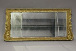 A 19th century George II style giltwood and gesso three-section overmantel mirror, the shaped