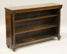 A George IV mahogany open bookcase, the two fixed shelves flanked by turned columns, on bun feet,
