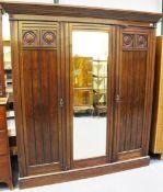 A late Victorian Aesthetic Movement walnut and ebonized three-section wardrobe, the interior