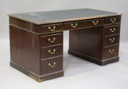 A mid-20th century reproduction mahogany twin-pedestal desk, fitted with an arrangement of nine