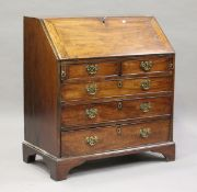 A small George III mahogany bureau, the fall-flap enclosing a fitted interior above oak-lined