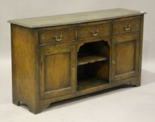 An 18th century style oak dresser base, the three drawers above an open shelf flanked by