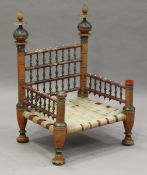 A late 19th/early 20th century Indian painted and turned wooden wedding chair with woven strap seat,