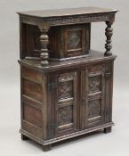 A 20th century Jacobean Revival oak side cupboard, fitted with three carved doors, height 112cm,
