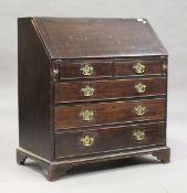 A George III oak bureau, the fall-flap above two short and three long drawers, on bracket feet,