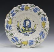 A Dutch Delft royal portrait dish, late 17th century, of circular shape, moulded with two rows of