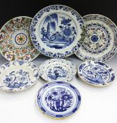 Seven assorted Dutch Delft chargers and plates, mid to late 18th century, comprising two