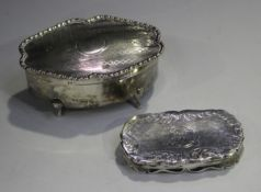 A George V silver trinket box of shaped oval form with engine turned decoration, raised on scroll