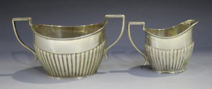 An Edwardian silver oval half-reeded two-handled sugar bowl and matching milk jug, Birmingham 1901