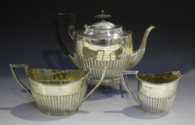 An Edwardian silver oval half-reeded three-piece tea set, comprising teapot, two-handled sugar